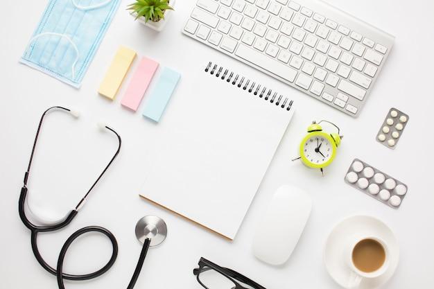 Equipo médico y suministros de oficina con taza de café sobre el escritorio del médico.