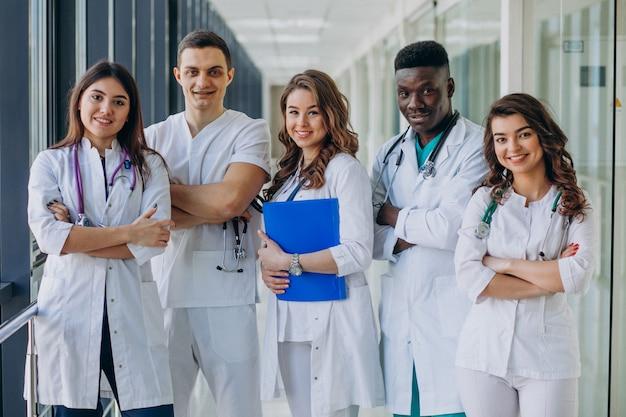 Equipo de médicos especialistas jóvenes de pie en el pasillo del hospital.