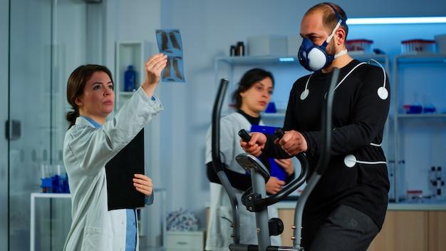 Equipo de médicos investigadores que supervisan la resistencia de los deportes de rendimiento del hombre con máscara que corre elíptica