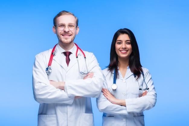 Un equipo de médicos jóvenes. gente multinacional - médico, enfermera y cirujano en fondo azul. un grupo de estudiantes de medicina de diferentes nacionalidades está mirando en la celda.