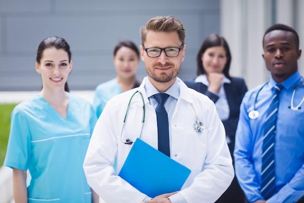 Equipo de médicos parados juntos en las instalaciones del hospital