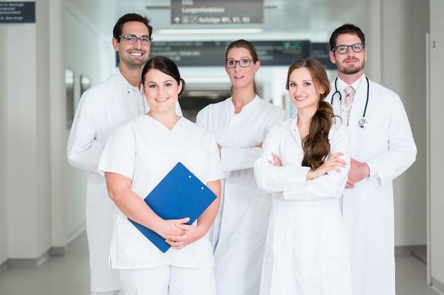Equipo de médicos de pie en el pasillo del hospital