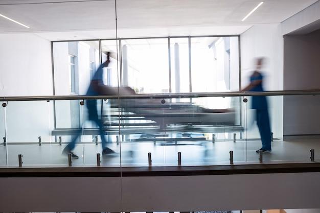 Equipo de médicos que llevan a una mujer embarazada al quirófano