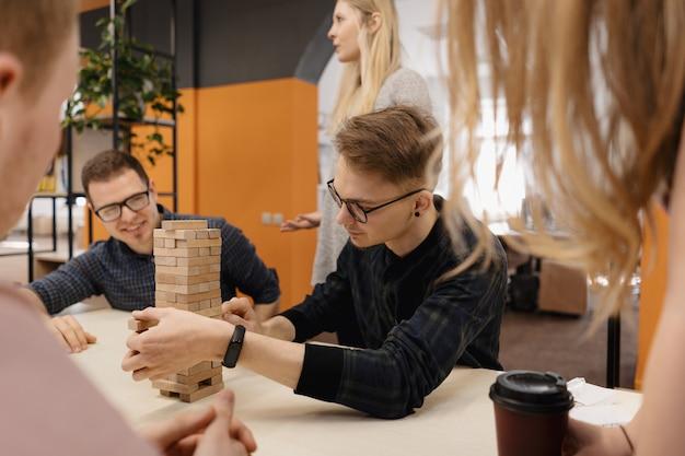 Equipo mixto jugando bloques juego de madera en la oficina
