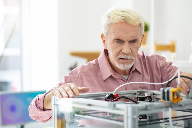 Equipo moderno. hombre mayor agradable apoyado en la impresora 3d y mirando dentro de ella, mientras imprime algo