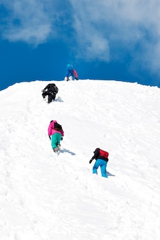 Un equipo de montañeros de cuerda sube hacia la cima