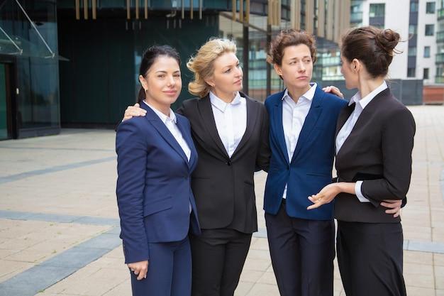 Equipo de mujeres empresarias de pie juntas al aire libre, apoyándose mutuamente, discutiendo el proyecto. vista frontal. concepto de comunidad y trabajo en equipo