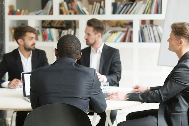 Equipo multiétnico de compañeros de trabajo masculinos que discuten planes corporativos durante la sesión informativa.