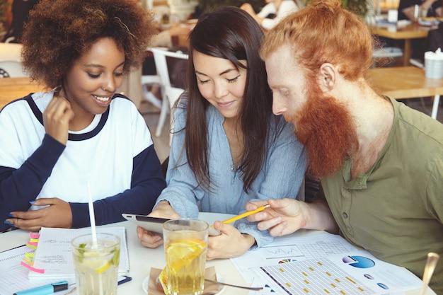 Equipo multiétnico de jóvenes emprendedores ambiciosos que trabajan juntos en la puesta en marcha del proyecto en la cafetería en la mesa con papeles de diagramas.
