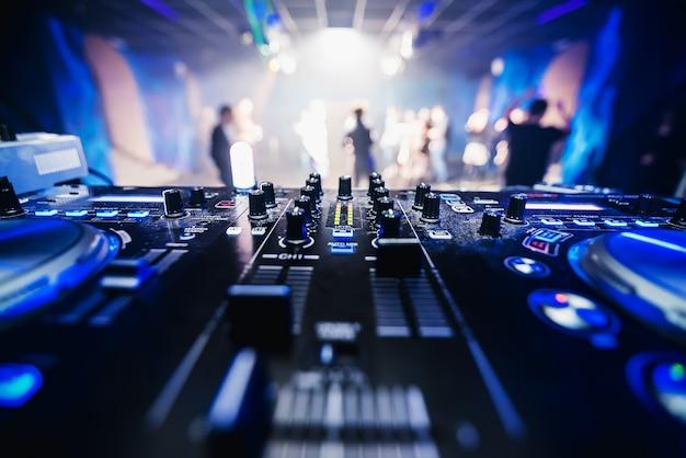 Equipo de música dj en discoteca closeup con gente de baile borrosa