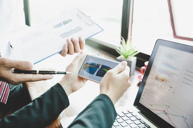 Equipo del negocio que analiza tablas y gráficos de la renta en smartphone. de cerca.