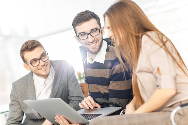 Equipo de negocios amigable que trabaja en la computadora portátil y discute asuntos comerciales.