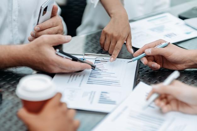Equipo de negocios analizando gráficos financieros de cerca