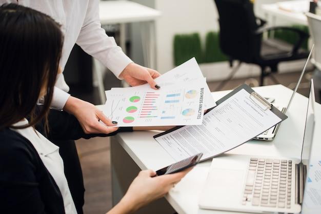 Equipo de negocios analizando gráficos de ingresos con computadoras portátiles modernas.