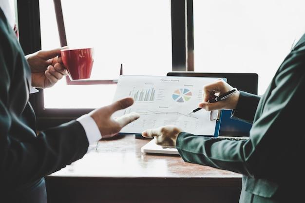 Equipo de negocios analizando tablas de ingresos y gráficos.