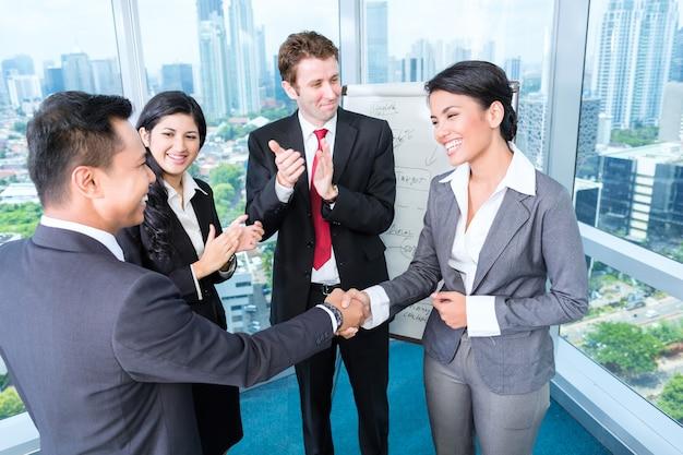 Equipo de negocios aplausos en reunión.