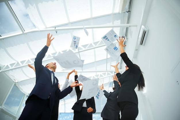 El equipo de negocios arroja los gráficos financieros a la cima.