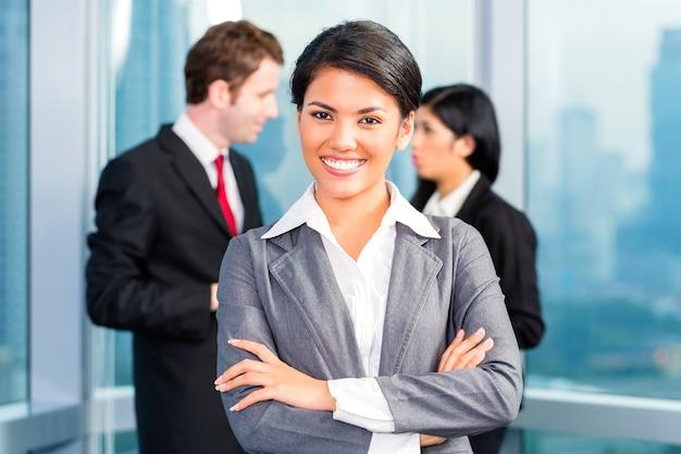 Equipo de negocios asiáticos en oficina, mujer en frente con horizonte
