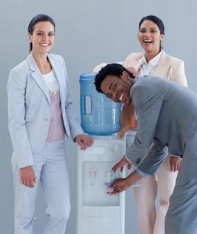Equipo de negocios bebiendo de un enfriador de agua