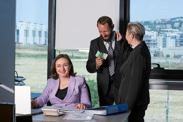 Equipo de negocios casual riendo durante la reunión. gente de negocios trabajando en la oficina. foto de tres colegas discutiendo sobre el proyecto, riendo felices socios comerciales. hombre feliz pagando 50 ils