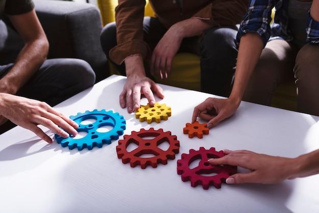 El equipo de negocios conecta piezas de engranajes, trabajo en equipo, asociación e integración, concepto