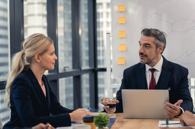 Equipo de negocios corporativos y gerente en una reunión. equipo joven de compañeros de trabajo haciendo una gran discusión de negocios en la oficina moderna de coworking. concepto de personas de trabajo en equipo