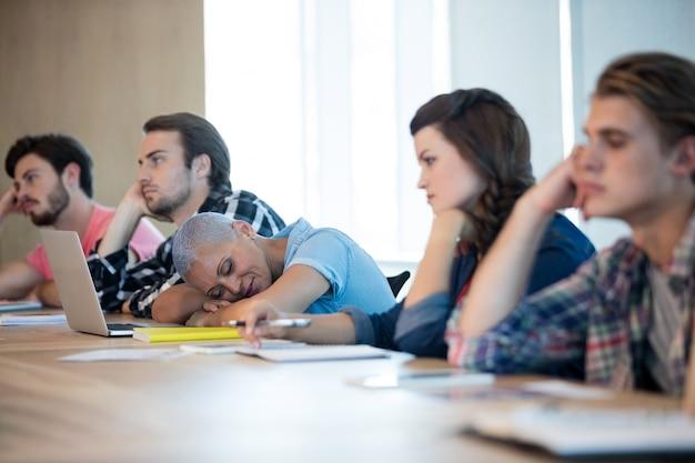Equipo de negocios creativo aburrido que asiste a una reunión en la sala de conferencias