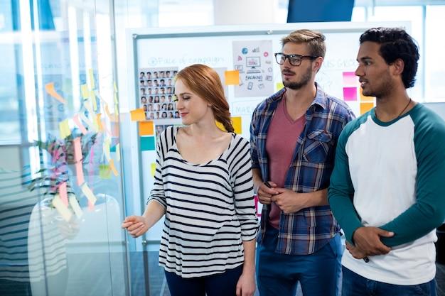 Equipo de negocios creativos en desuso sobre las notas adhesivas en la oficina