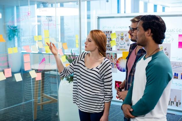 Equipo de negocios creativos escribiendo en las notas adhesivas en office
