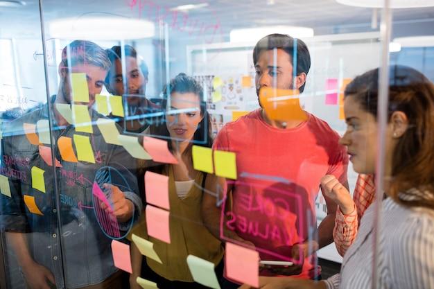 Equipo de negocios creativos mirando notas adhesivas en la ventana de vidrio en la oficina