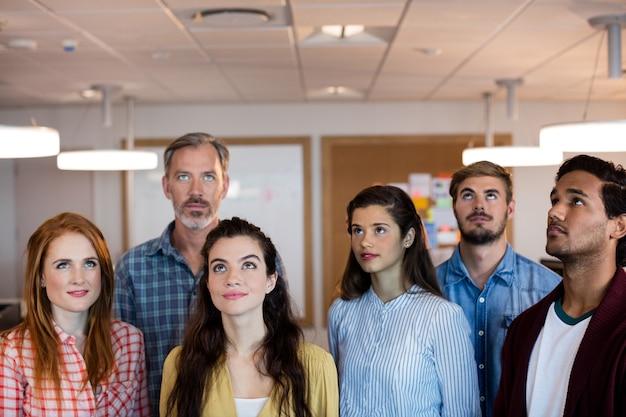 Equipo de negocios creativos de pie juntos y mirando hacia arriba en la oficina