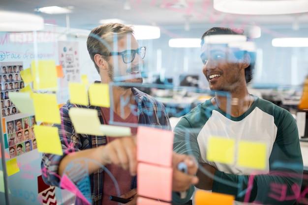 Equipo de negocios creativos sonriente leyendo notas adhesivas en la oficina
