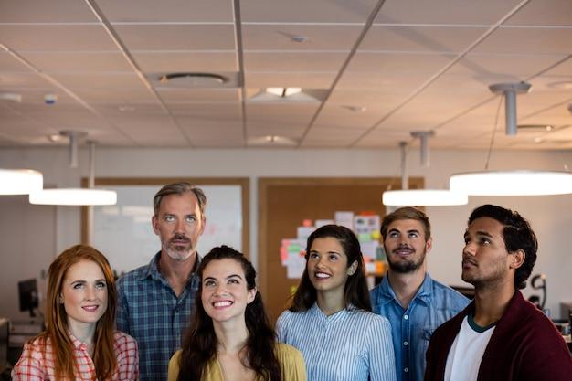 Equipo de negocios creativos sonrientes de pie juntos y mirando hacia arriba en la oficina