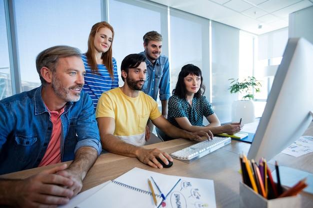 Equipo de negocios creativos trabajando juntos en la pc de escritorio en la oficina