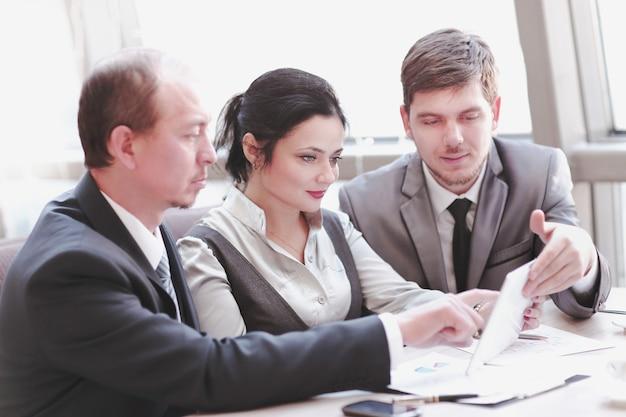 Equipo de negocios discutiendo gráficos financieros con tableta digital