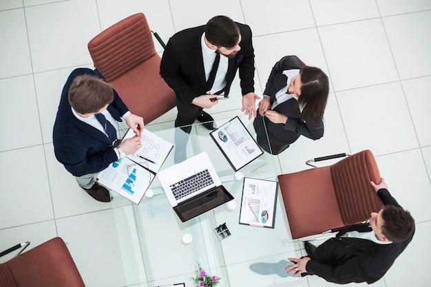 Equipo de negocios discutiendo gráficos de marketing en una reunión de trabajo.