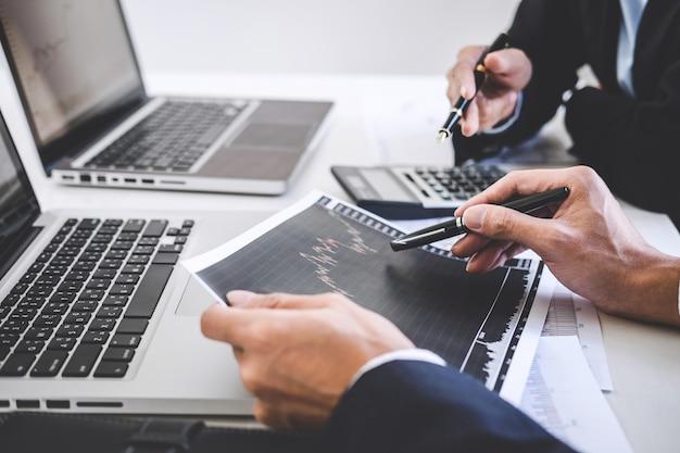 Equipo de negocios dos colegas que trabajan y analizan el mercado de valores gráfico