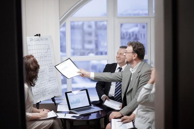 Equipo de negocios e inversores discutiendo las ganancias de la empresa en una oficina moderna.