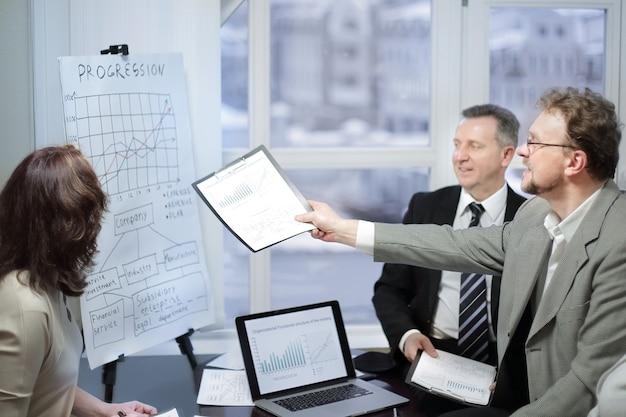 Equipo de negocios e inversores discutiendo las ganancias de la empresa en una oficina moderna