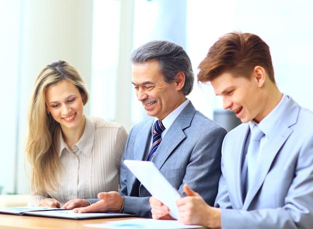 Equipo de negocios entrevistando a joven solicitante en oficina brillante