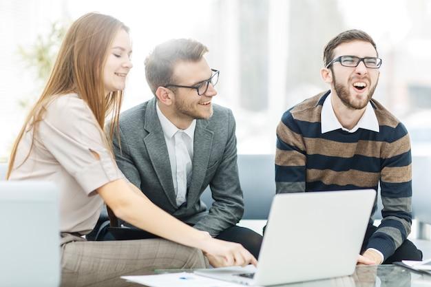 Equipo de negocios exitoso con computadora portátil en el lugar de trabajo discutir preguntas de trabajo