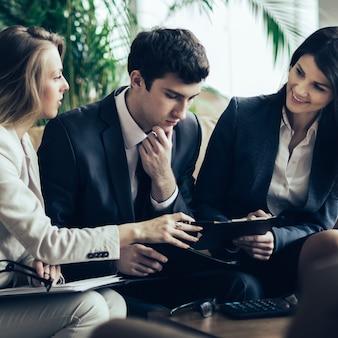 Equipo de negocios exitoso discutiendo documentos financieros sentado en el sofá en el vestíbulo de una oficina moderna
