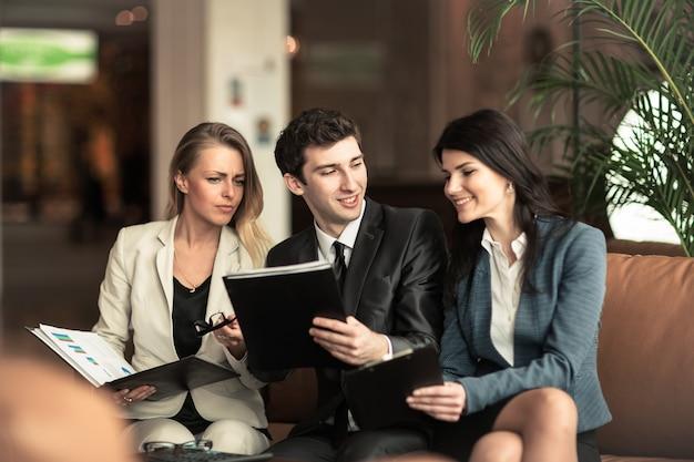 Equipo de negocios exitoso discutiendo documentos financieros sentado en el sofá