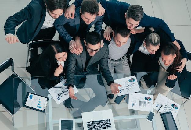 Equipo de negocios exitoso sentado en un escritorio y mirando a la cámara