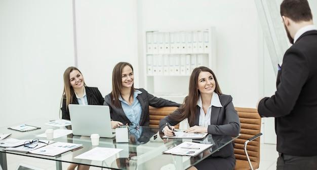 Equipo de negocios exitoso en el taller escuchando al jefe.