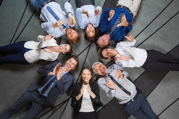 Equipo de negocios se extiende en el piso y que aplaude