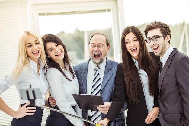 Equipo de negocios feliz hace un selfie con su jefe de pie cerca de la ventana en la oficina