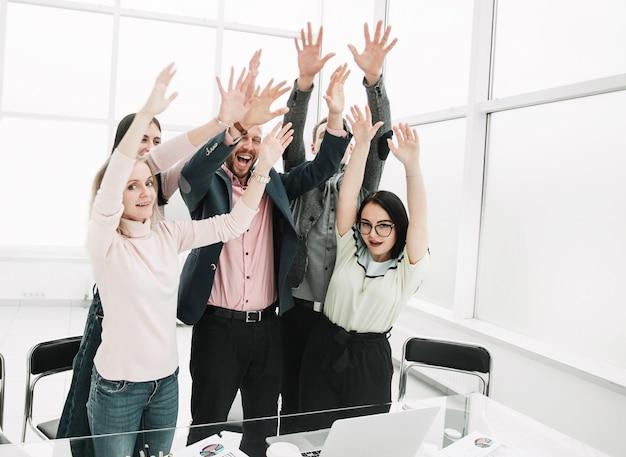 Equipo de negocios feliz con las manos en alto mostrando su desempeño exitoso. el concepto de trabajo en equipo