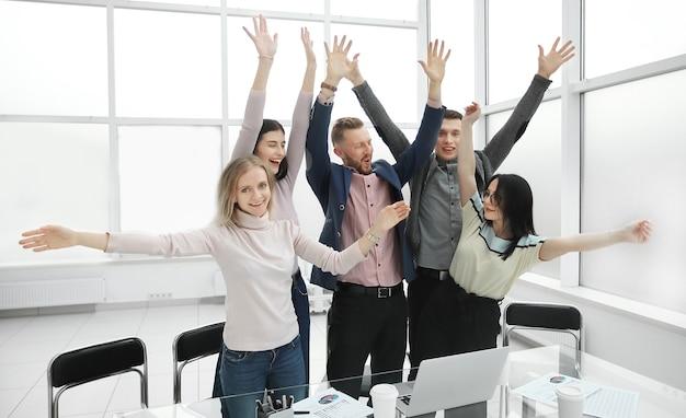 Equipo de negocios feliz mostrando su éxito cerca del escritorio