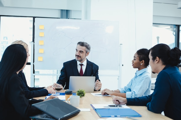 Equipo de negocios y gerente en sala de reuniones.